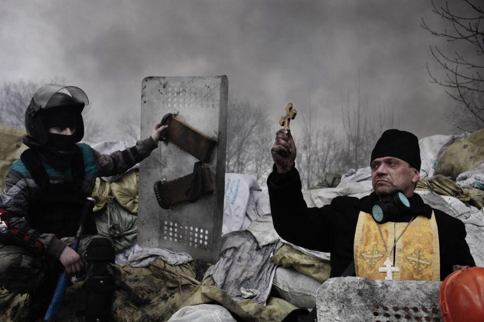El fotógrafo francés Jerome Sessini, de la agencia Magnum, ha ganado el segundo premio en la categoría de noticias de actualidad. Un sacerdote ortodoxo bendice a los manifestantes en una barricada en Kiev (Ucrania) el 20 de febrero de 2014.